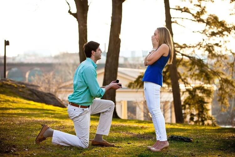Woman shocked by her partner's surprise proposal in grounds of The Philadelphia Museum of Art in Philadelphia, USA