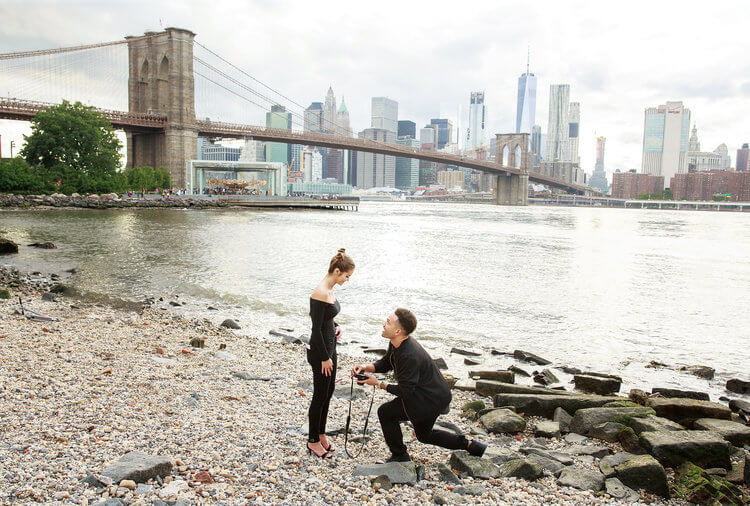 Man proposing to his partner on a pebble beach in Brooklyn, New York City USA