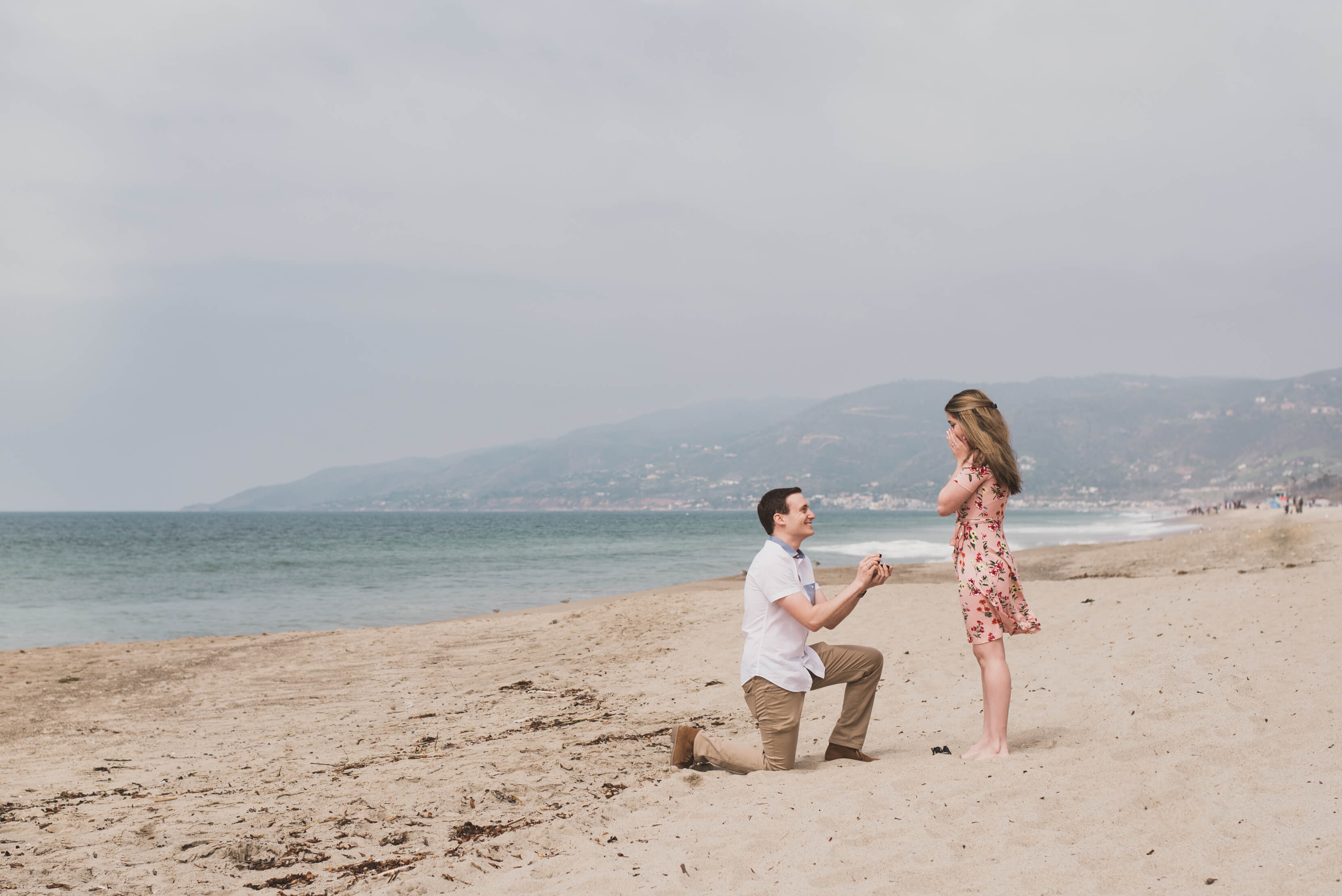 Man proposing to his partner at a beach in Los Angeles, California USA