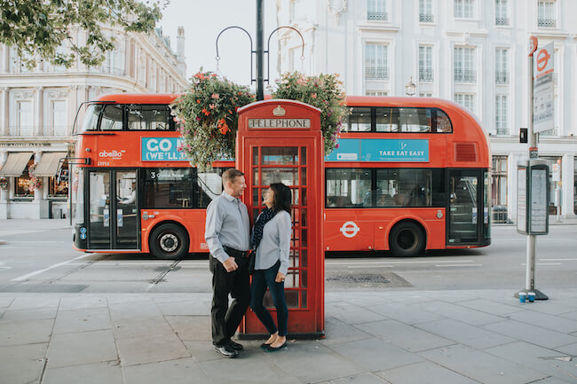 Couple smiling at each other in front of iconic red phone booth with a red double-decker bus passing in the background in London on a couples trip