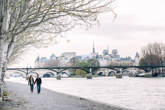 Couple holding hands and walking along the Siene river together in Paris, France on a couples trip