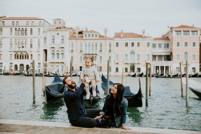 Family sitting together in front of gondola boats, holding their young daughter up in their arms on a family trip in Venice