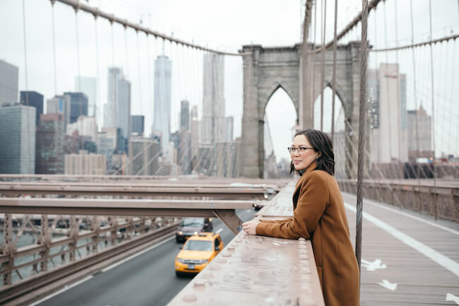 Woman smiling on a pedestrian walkway on the Brooklyn Bridge in New York City on a solo trip