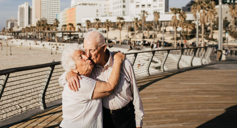 Elderly couple hugging one another and kissing on a beach boardwalk on a family photo shoot