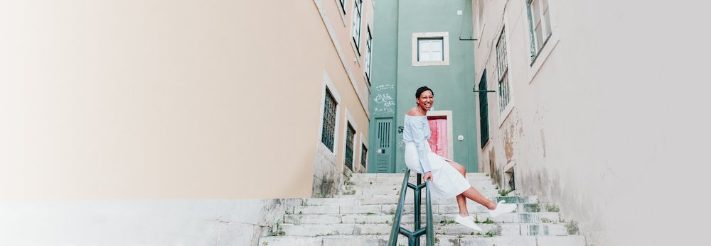 Happy woman sitting on a stairwell railing smiling with a colourful green wall in the background on a solo trip photo shoot