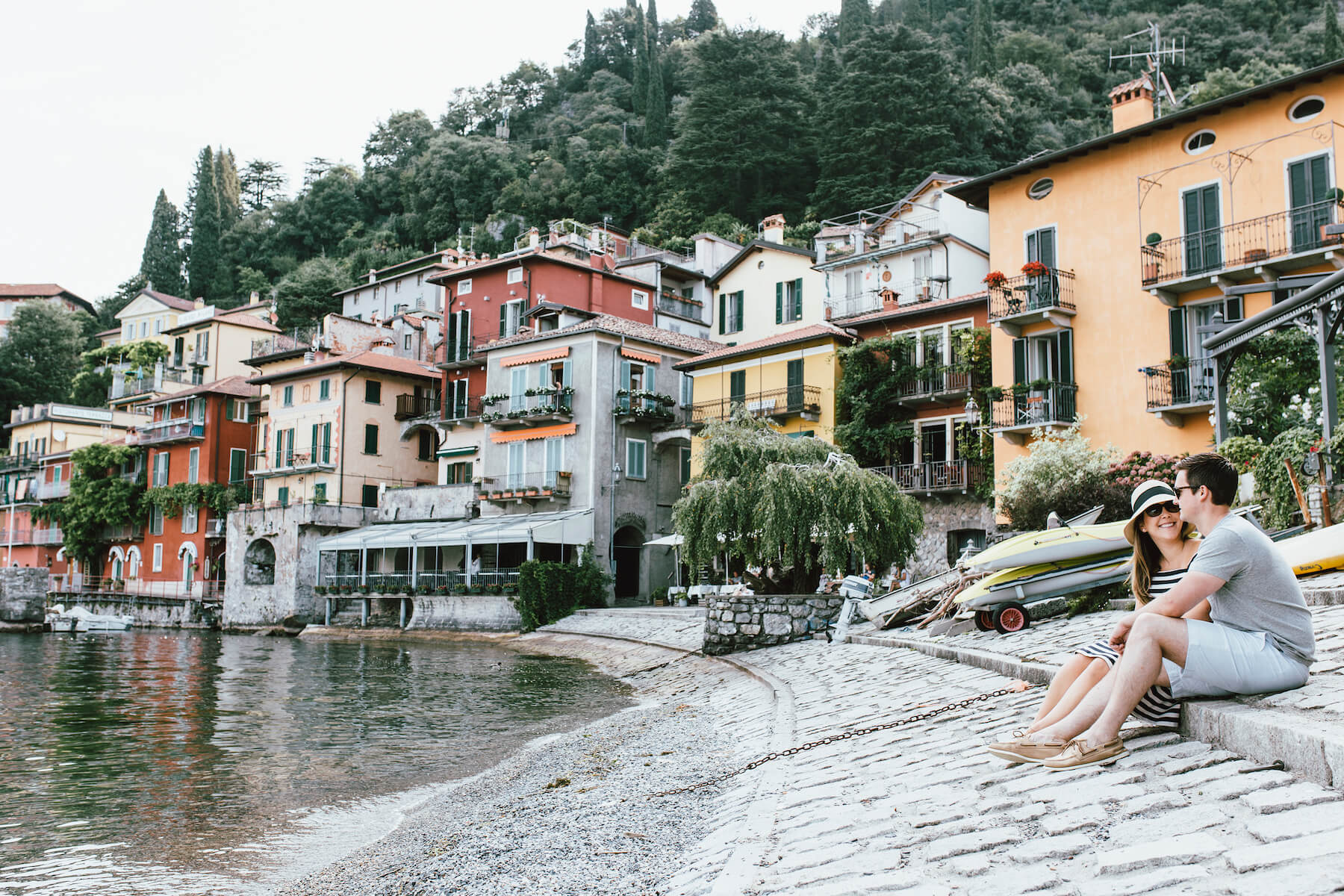couple sitting down on the beach in lake Como, Italy
