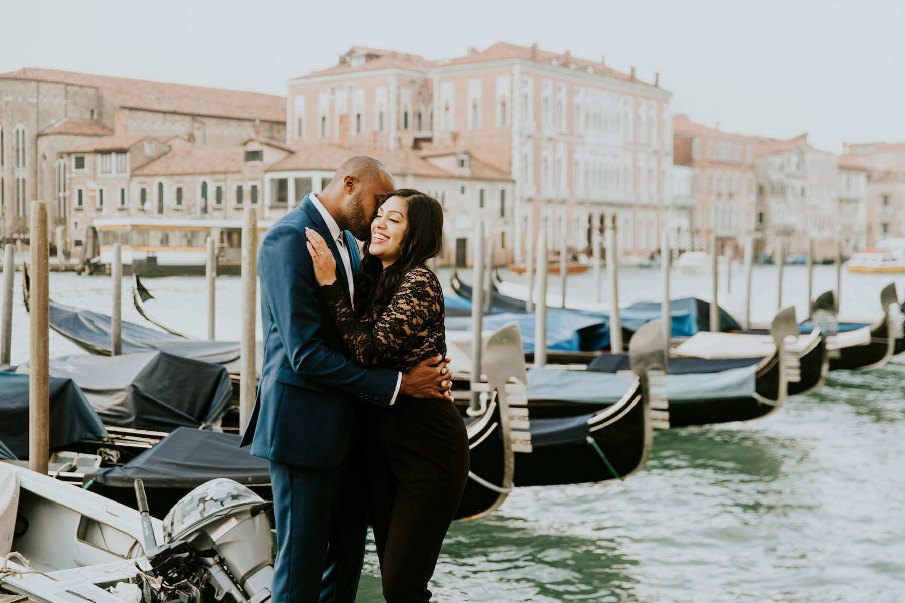 couple holding each other, the man is giving the lady a kiss in Venice, Italy