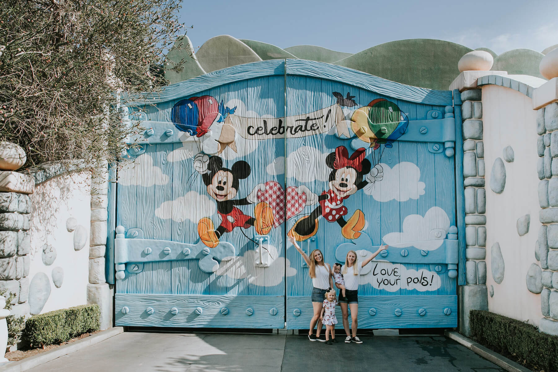 LGBTQ+ family with two young kids standing in front of a colourful door at Disneyland, Anaheim, California USA