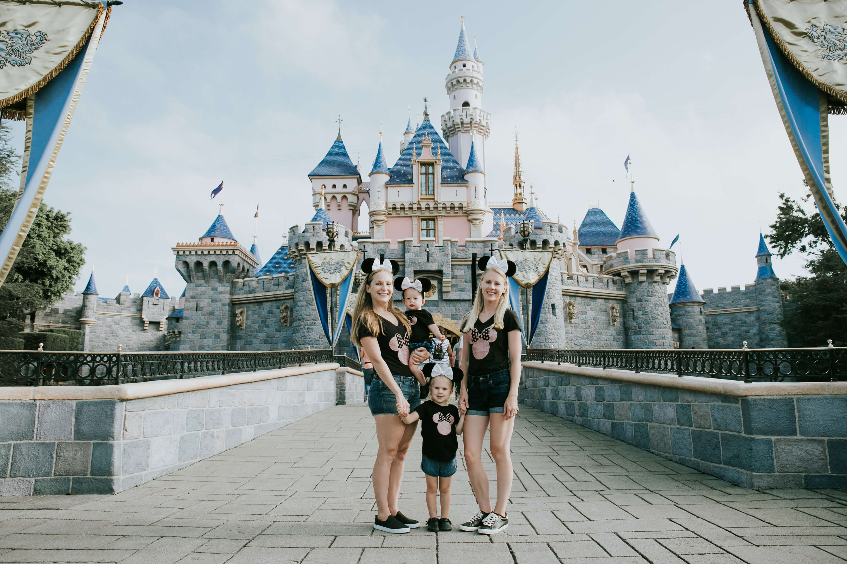 LGBTQ+ family with two young kids standing in front of the castle in Disneyland, Anaheim