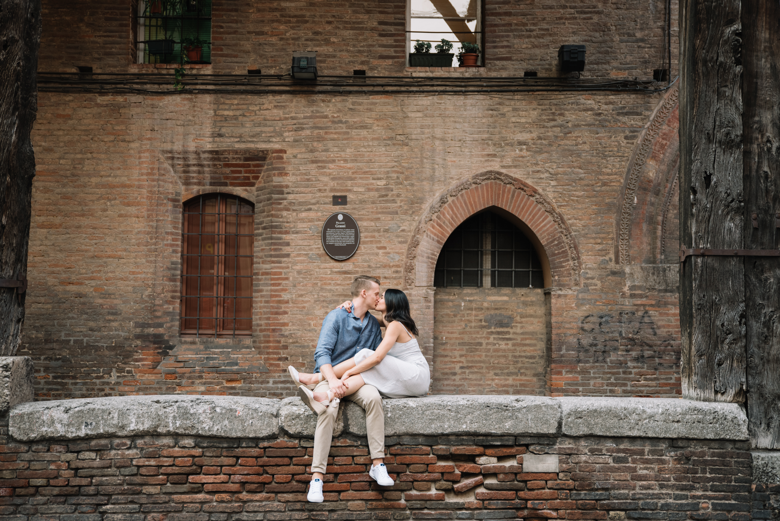 couple sitting on a ledge, kissing, in Bologna, Italy