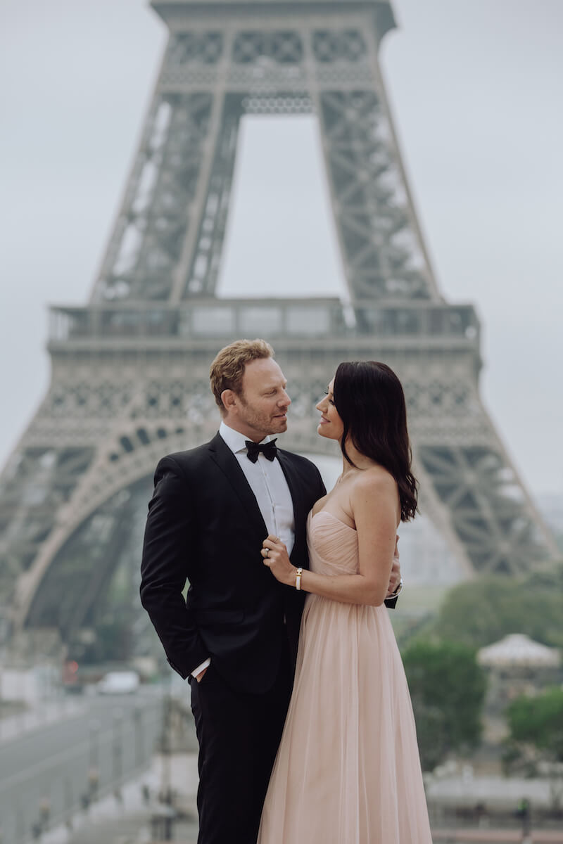 Couple holding each other in front of the Eiffel tower in Paris France