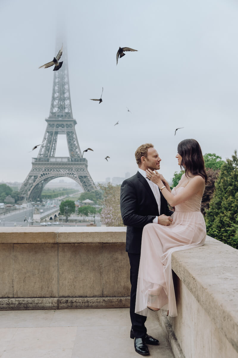 couple in front of Eiffel tower fixing bow tie in Paris France