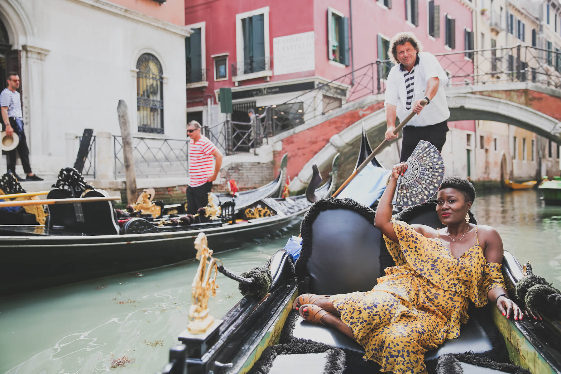 Woman in gold dress on a gondola boat in Venice, Italy