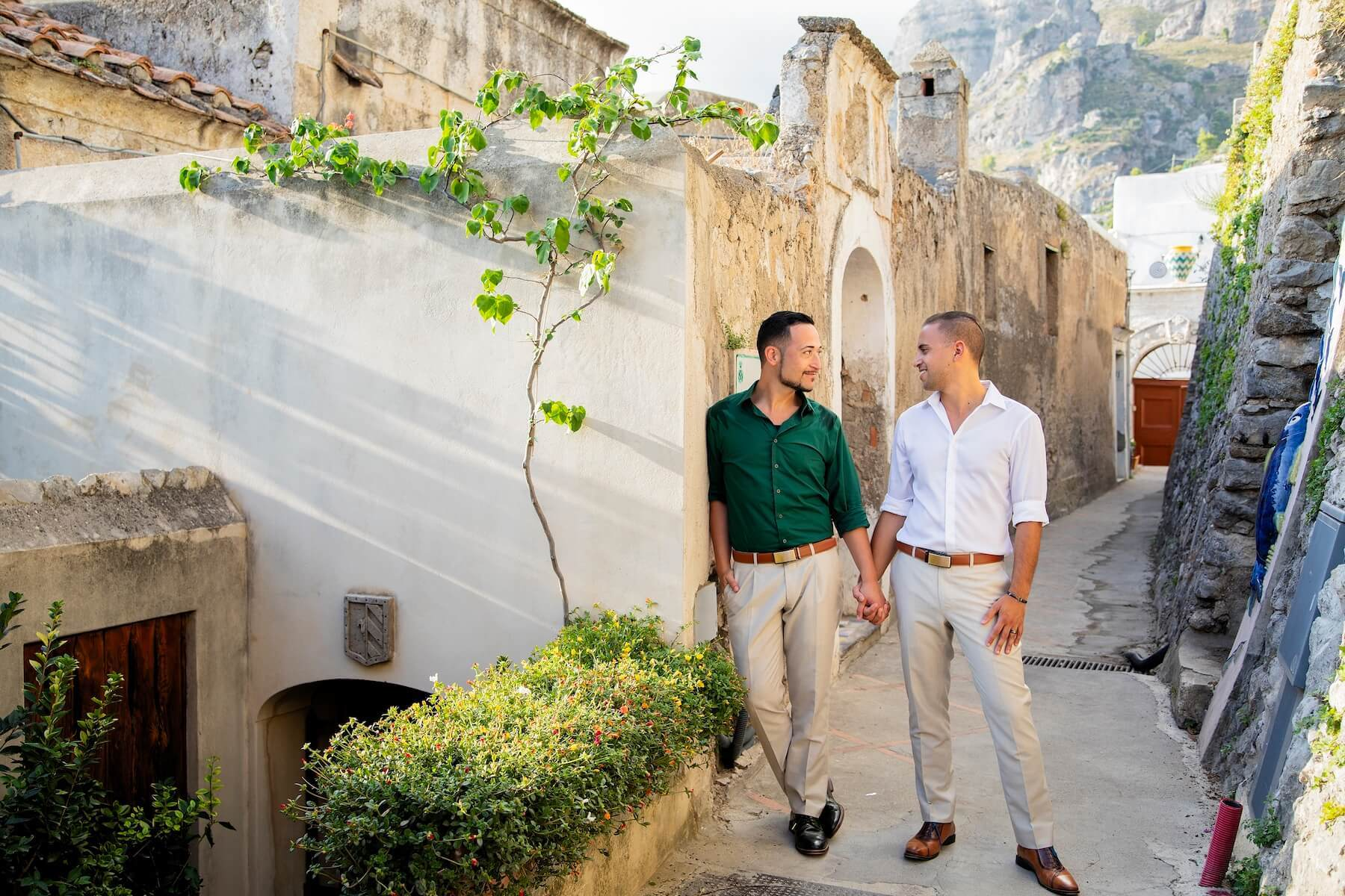 LGBTQ couple holding hands and standing in a small cobble street in Amalfi Coast, Italy