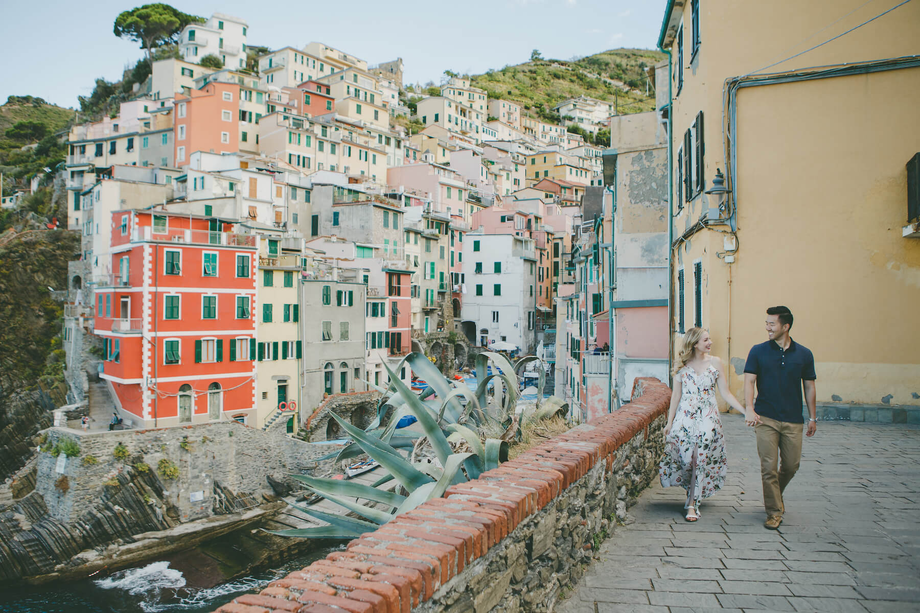 a couple walking and holding hands, with the background being colourful cliffside houses in Cinque Terre, Italy