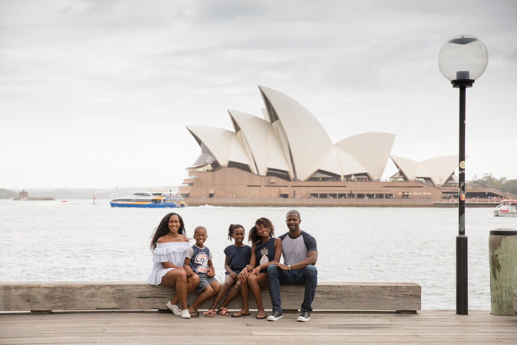 a family with young children sitting down and Sydney Opera house in the background in Sydney, Australia