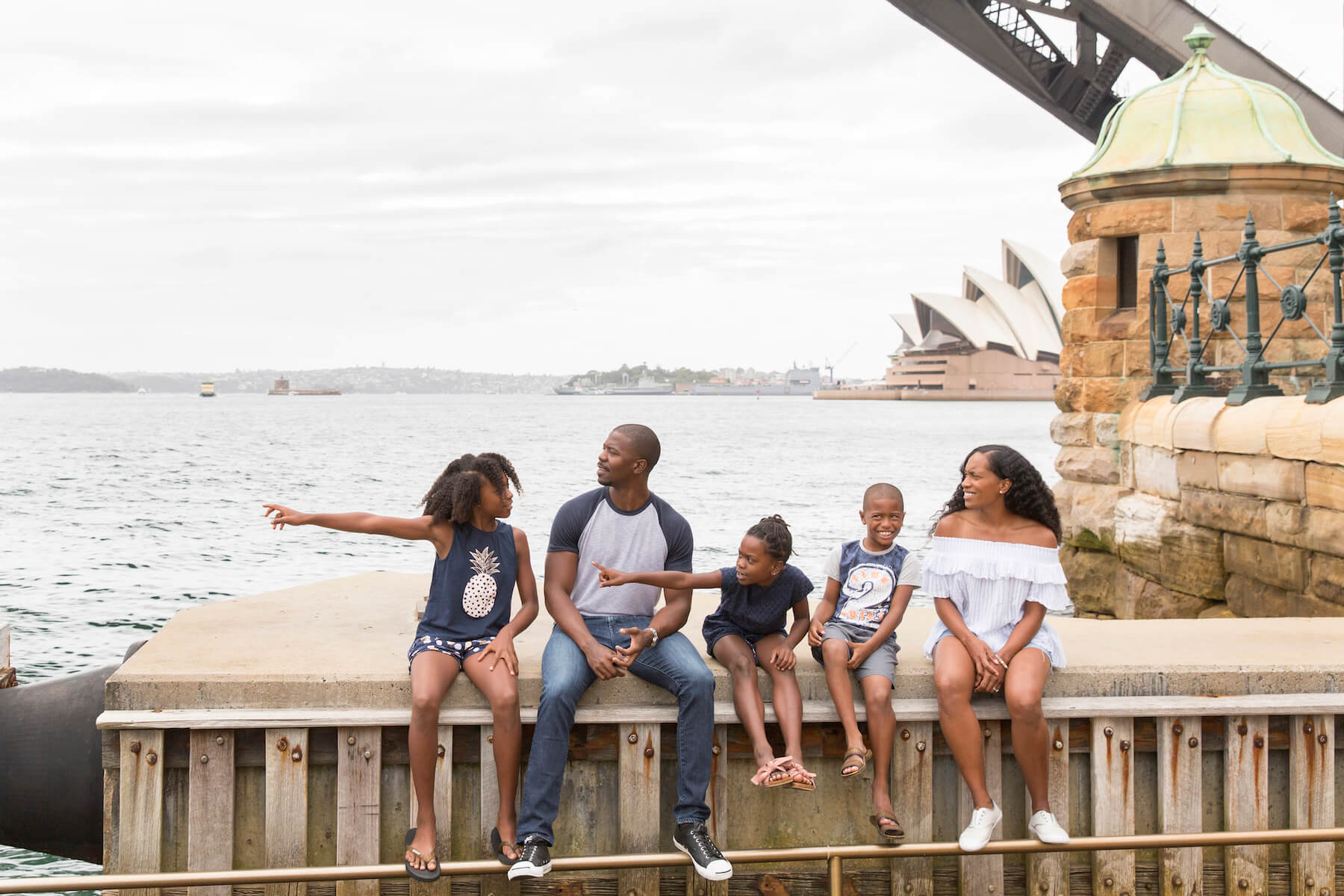 a family of four sitting on the wharf in Sydney, Australia
