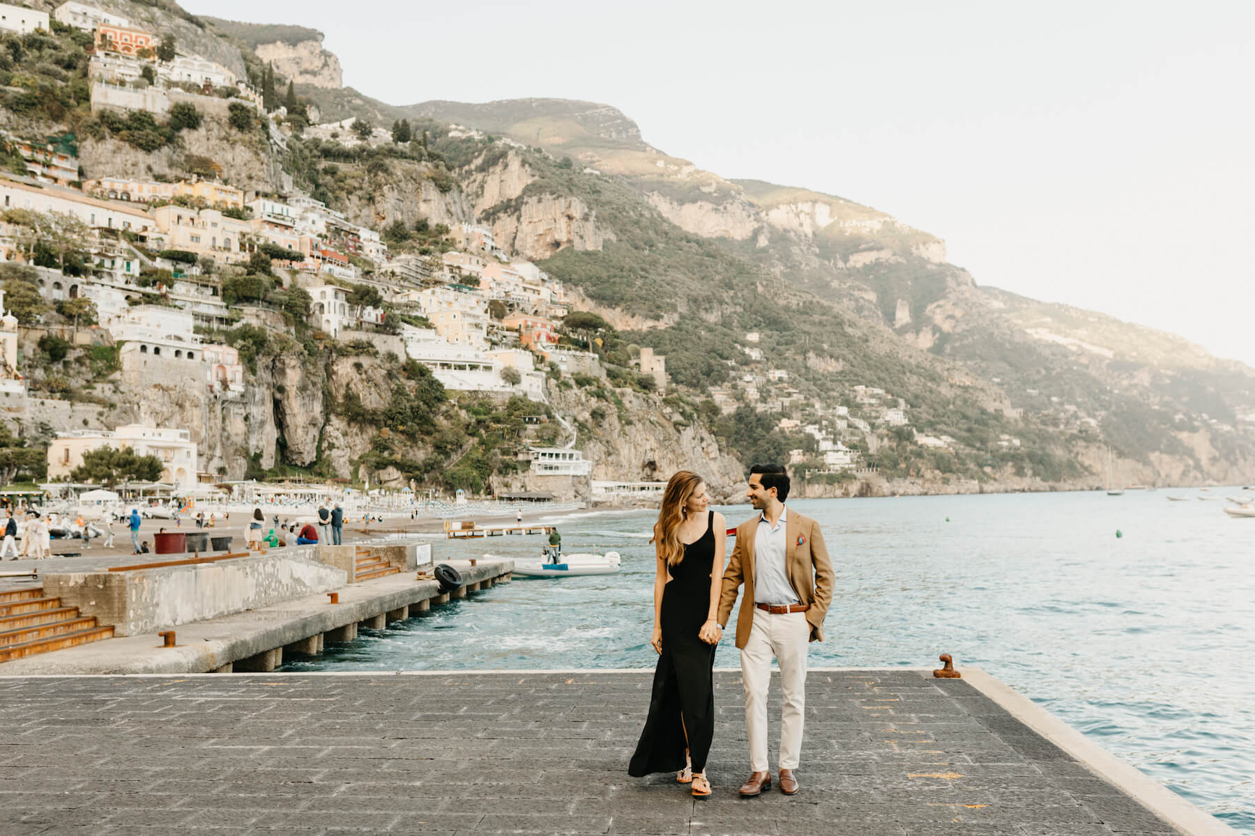 couple holding hands and walking on the beach in Positano, Italy