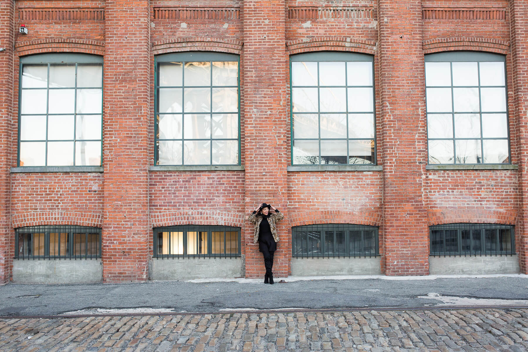 woman solo traveller standing against brick wall in New York City