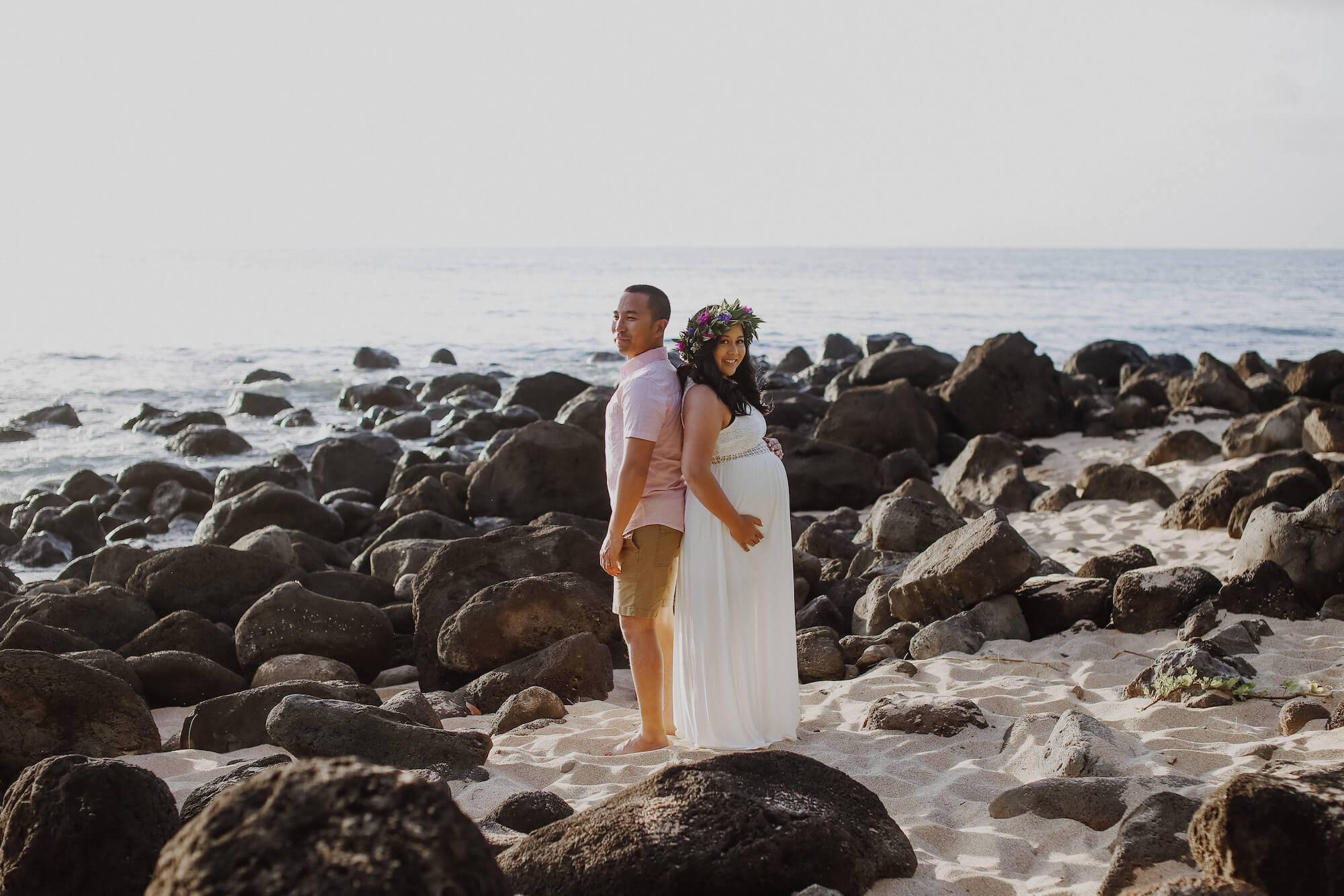 Couple standing back-to-back on rocks by the water on a babymoon photo shoot