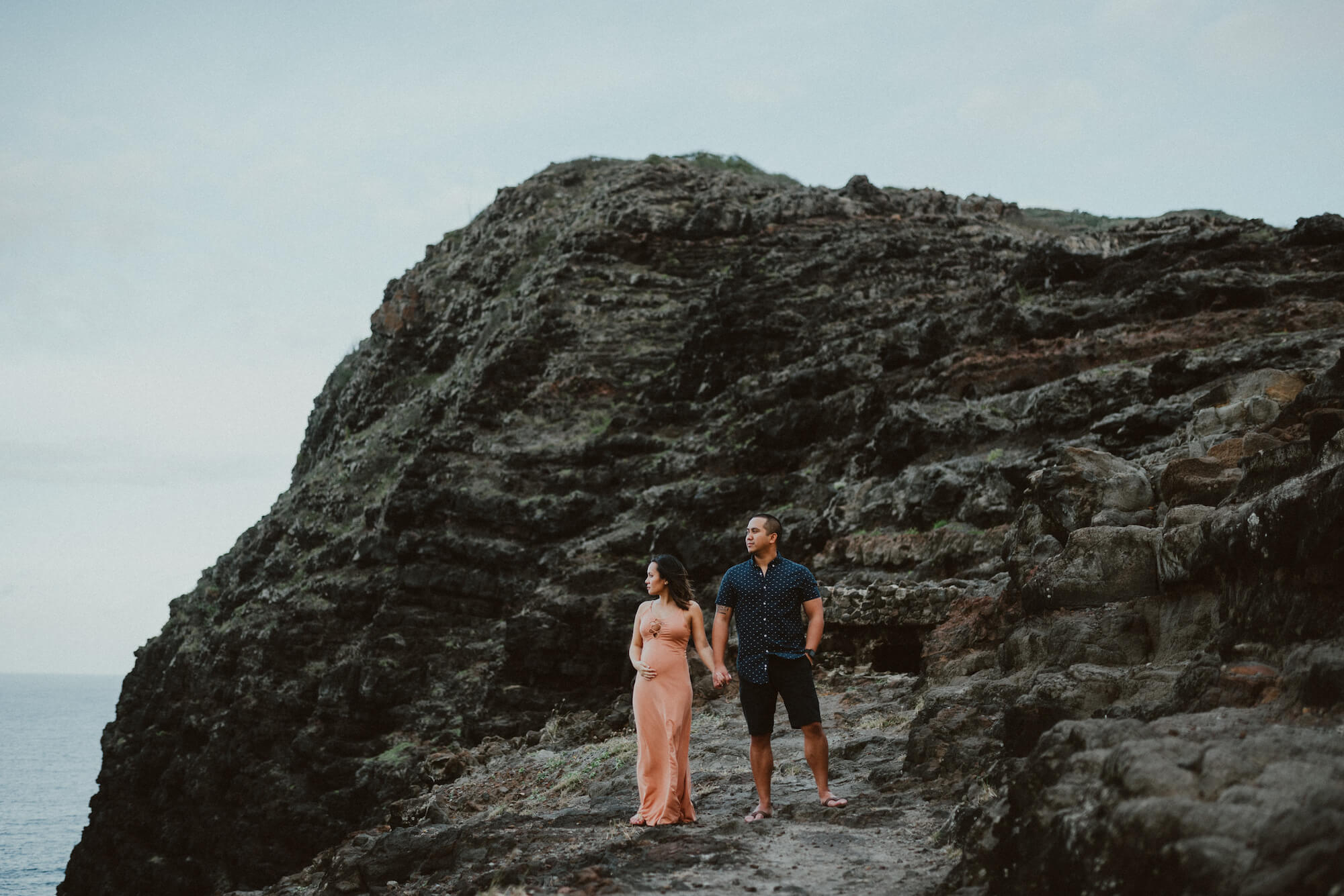 Man holding his female partner while they stand on rocks near the ocean shore together at sunset in Maui on a couples trip