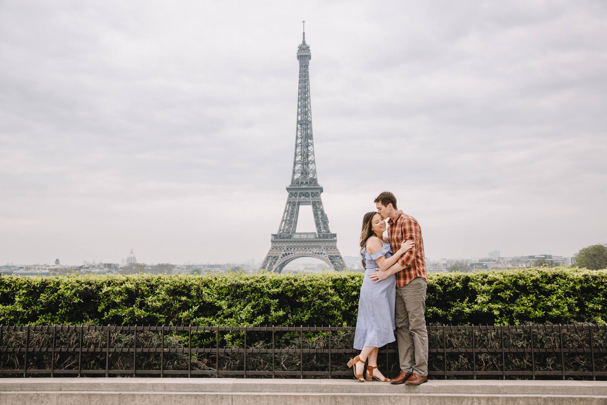Couple holding one another while the male partner kisses his wife's head with the Eiffel Tower in the background