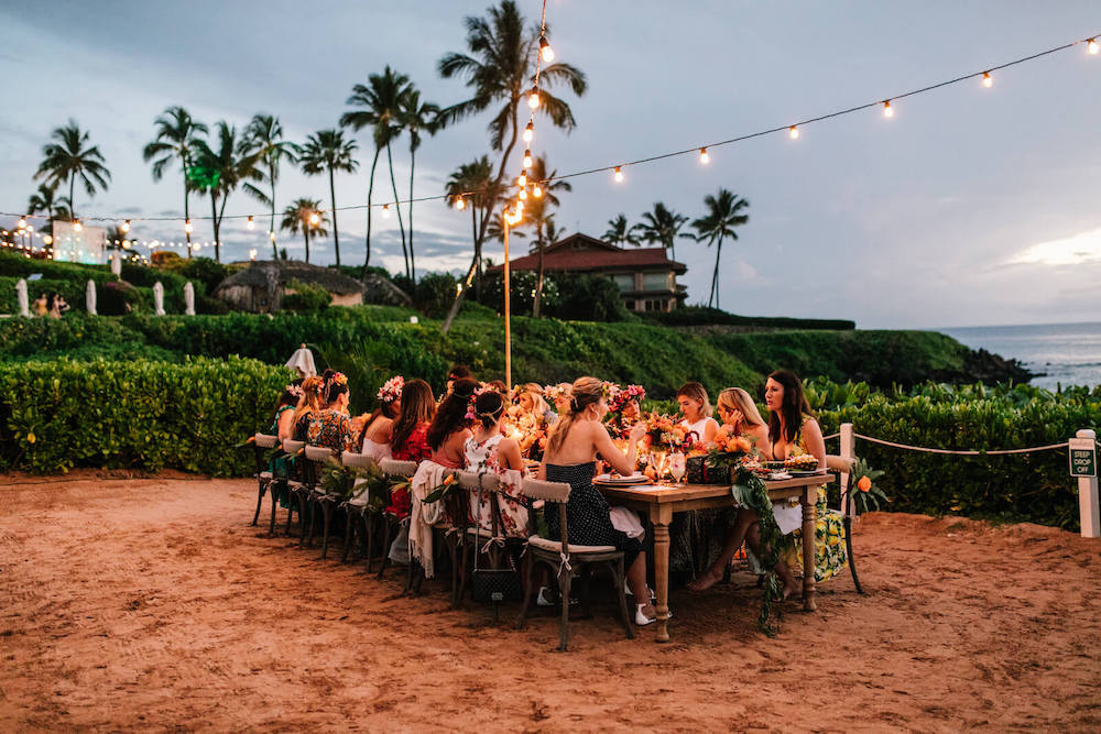 Large group of female friends gathered together at a table on a beach celebrating an event together with Flytographer Event Photography