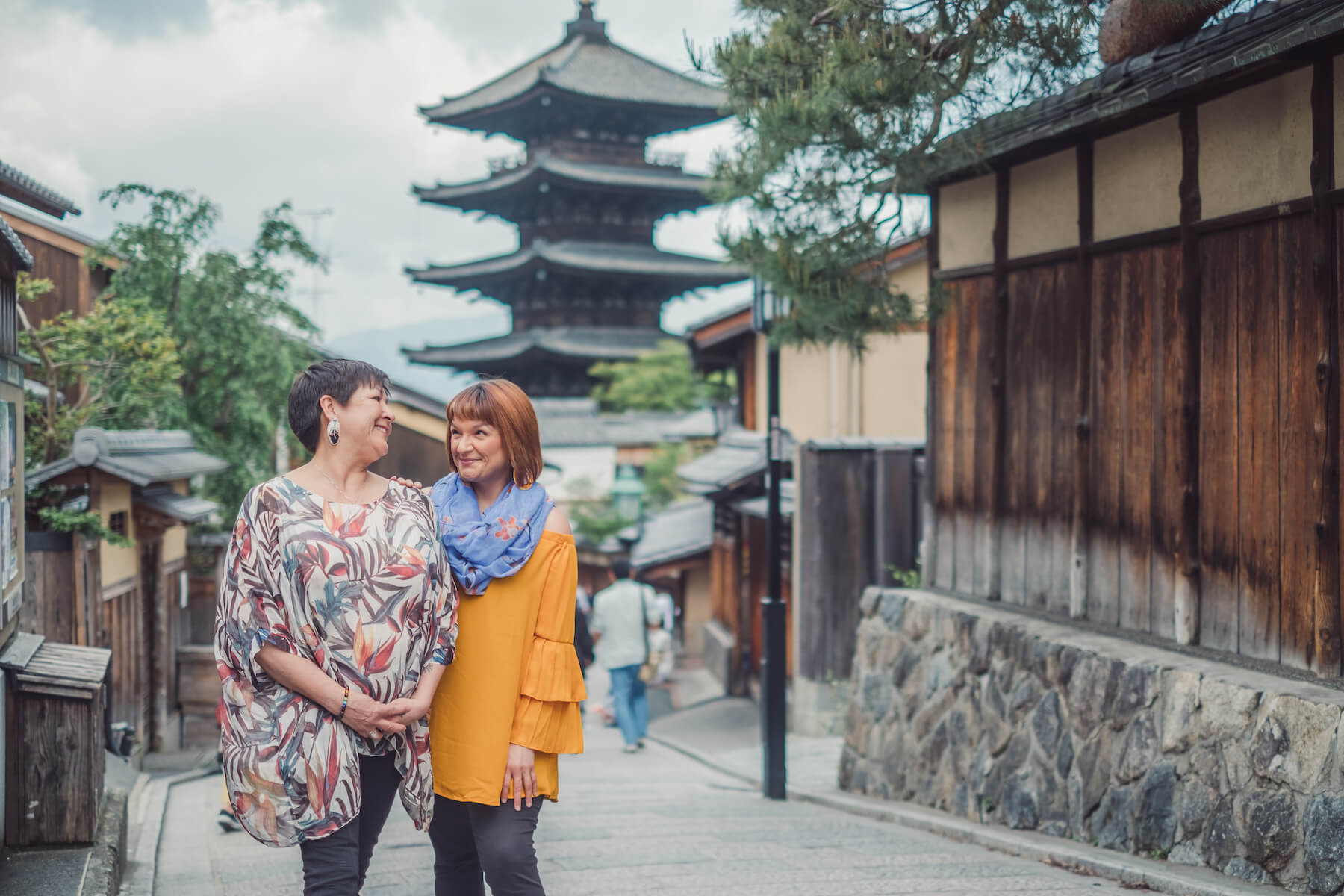 Girlfriends standing in front of temple in Kyoto Japan