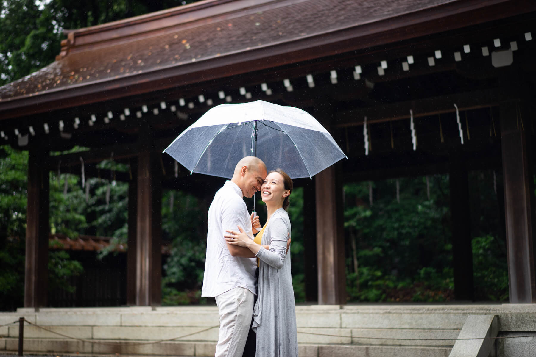 Couple embracing in the rain in front of temple, Tokyo Japan