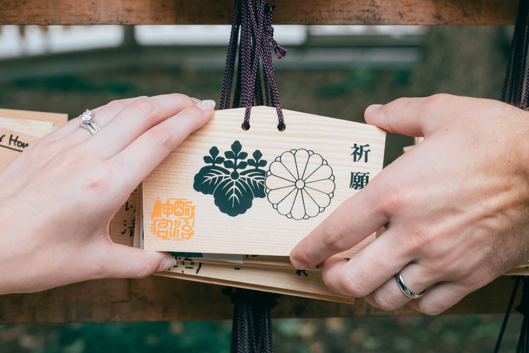 couple holding a sign at Meiji Shrine, Tokyo Japan