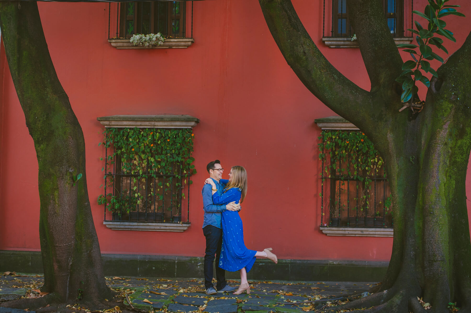 couple hugging each other in front of a colorful building in Mexico City, Mexico
