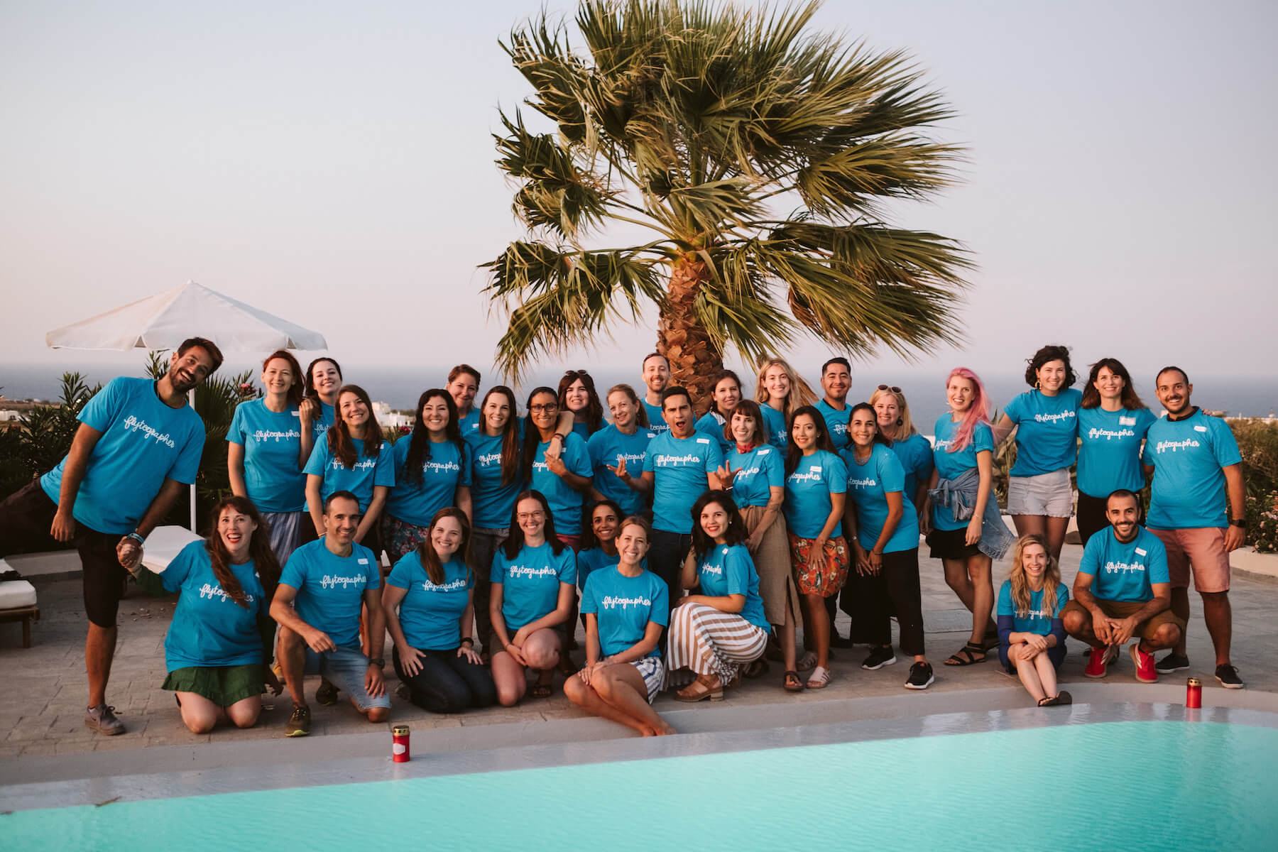 Group of people in blue t-shirts standing by a pool in Santorini, Greece