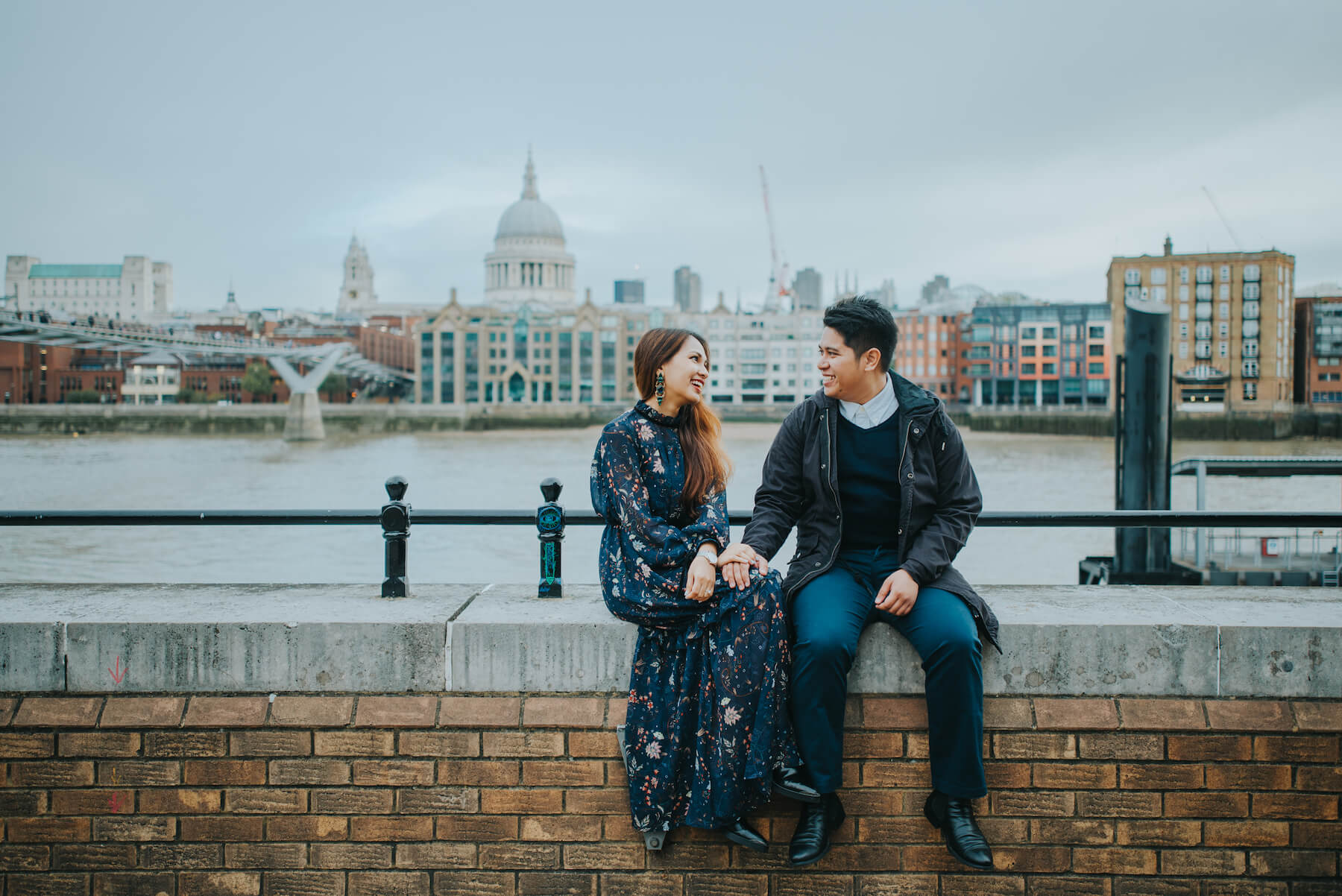 couple sitting on a bridge in London, England