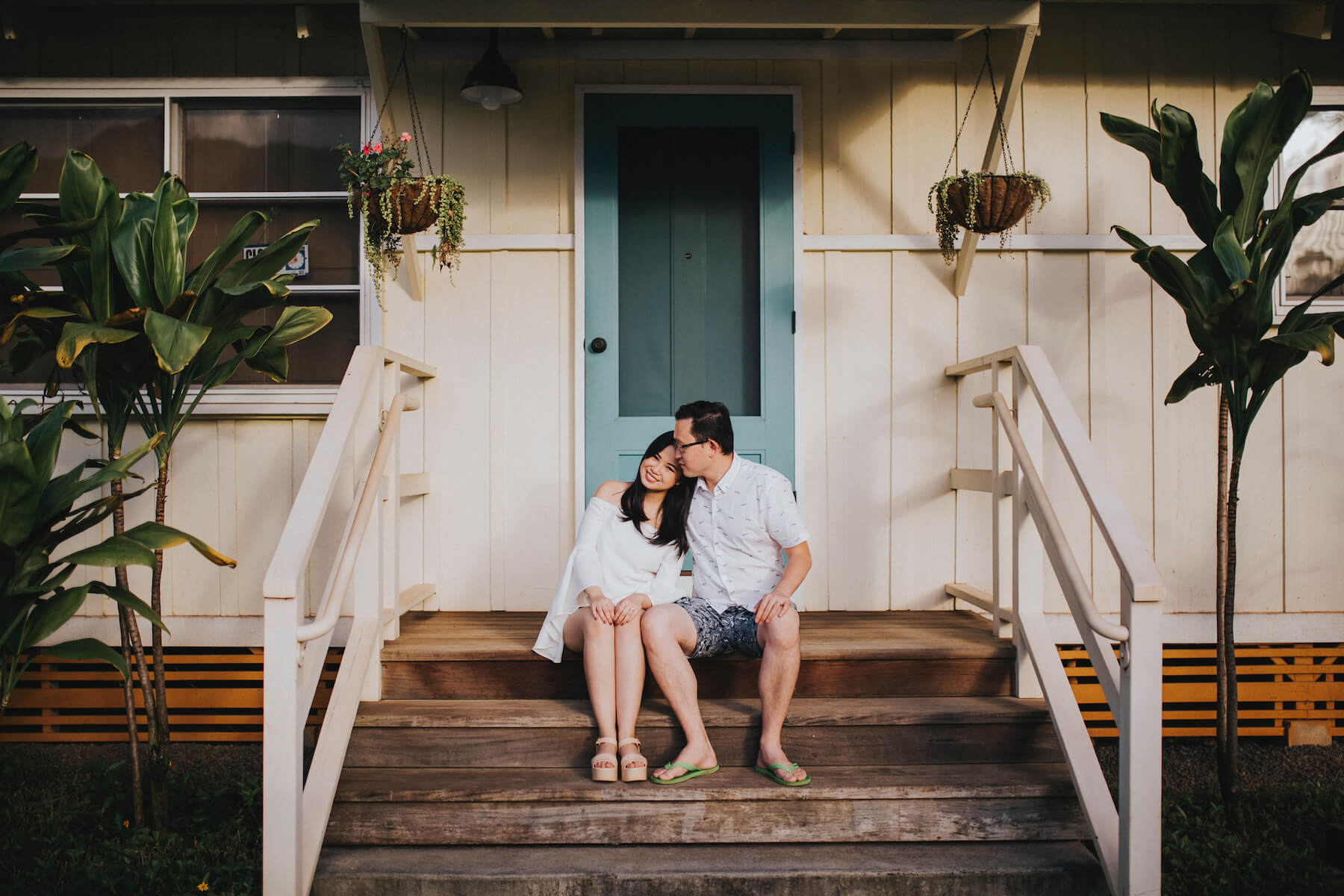 A couple sitting on a porch of a surf shack in Honolulu, Hawaii