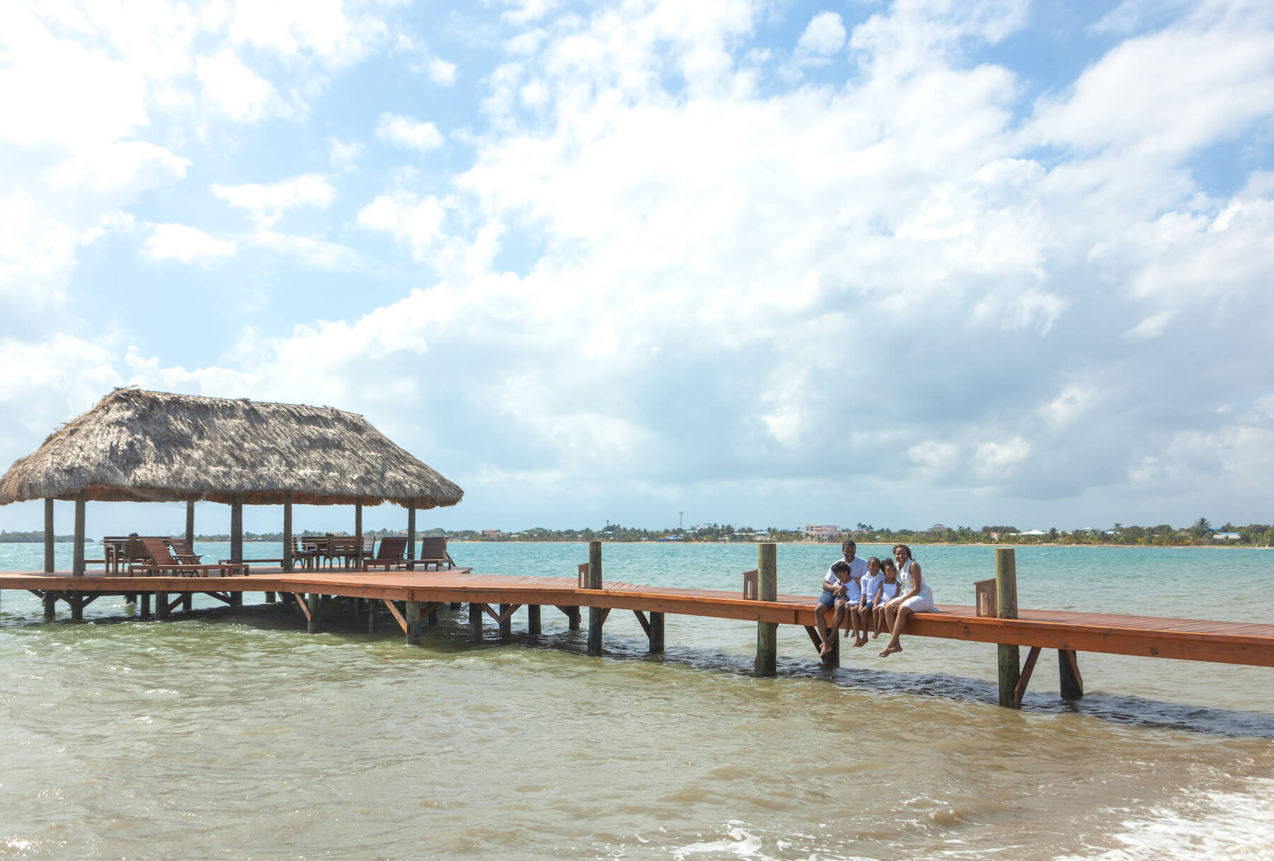 Family sitting on a dock in Placencia Belize