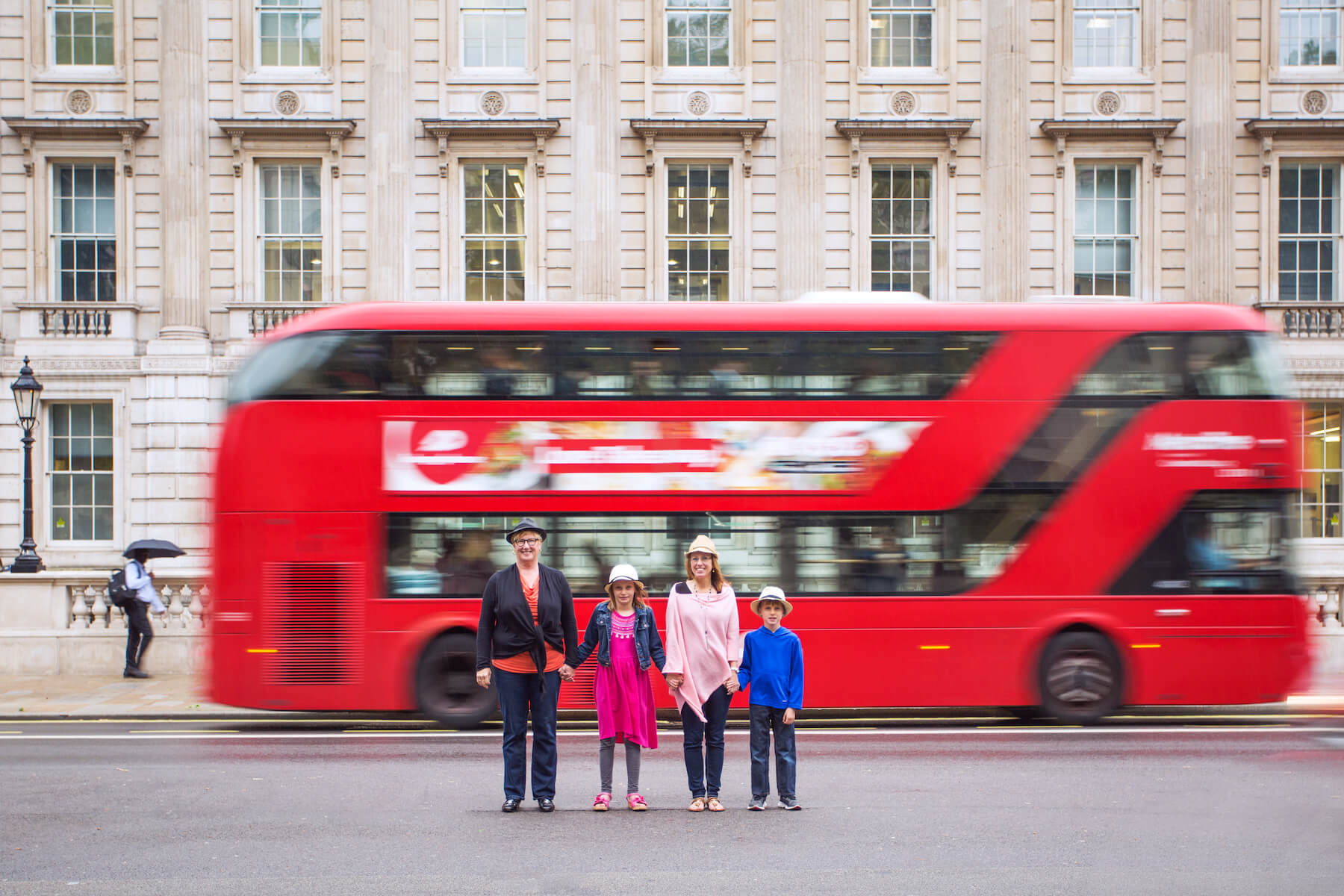family in front of a double decker bus in London, England