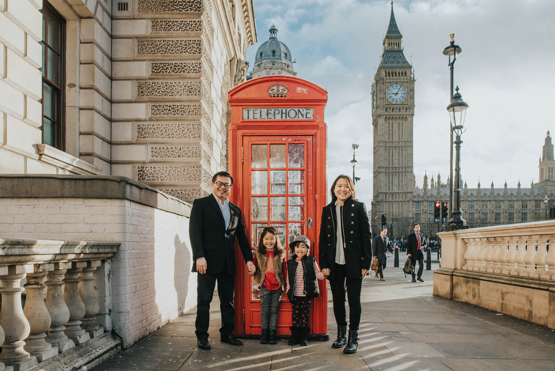 family standing in front of a red phone booth in London, England