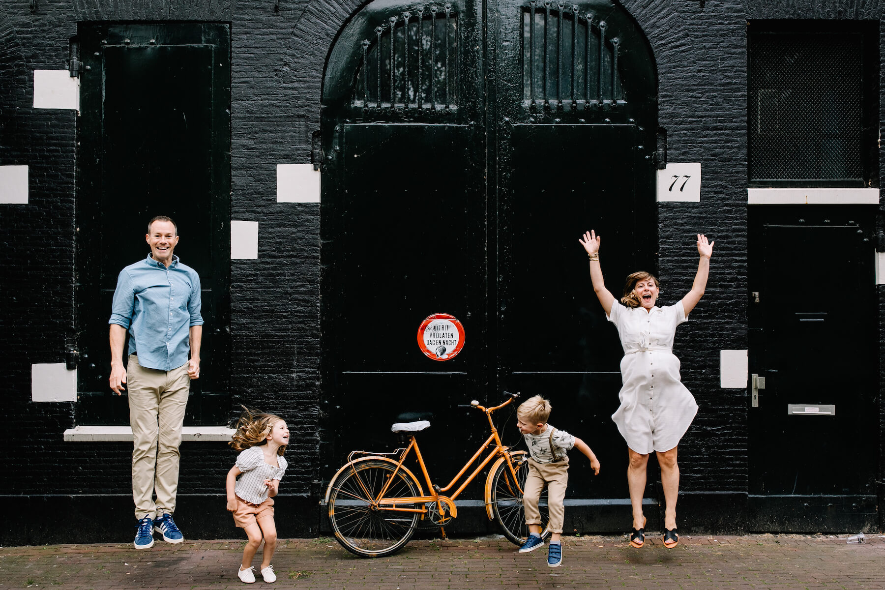 a family jumping and laughing in front of black brick building in Amsterdam, Netherlands