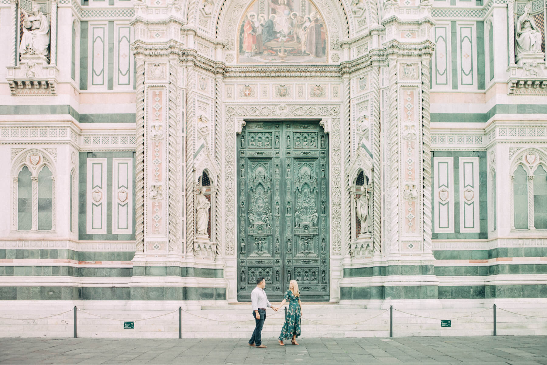 couple walking in front of the Duomo church in Florence, Italy
