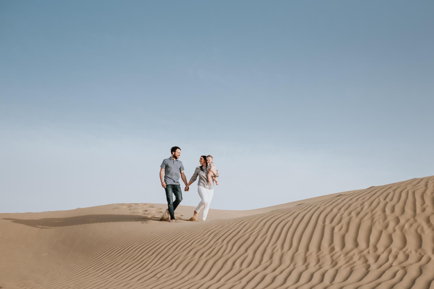 Family in Dubai walking in the desert holding a baby in Dubai, UAE