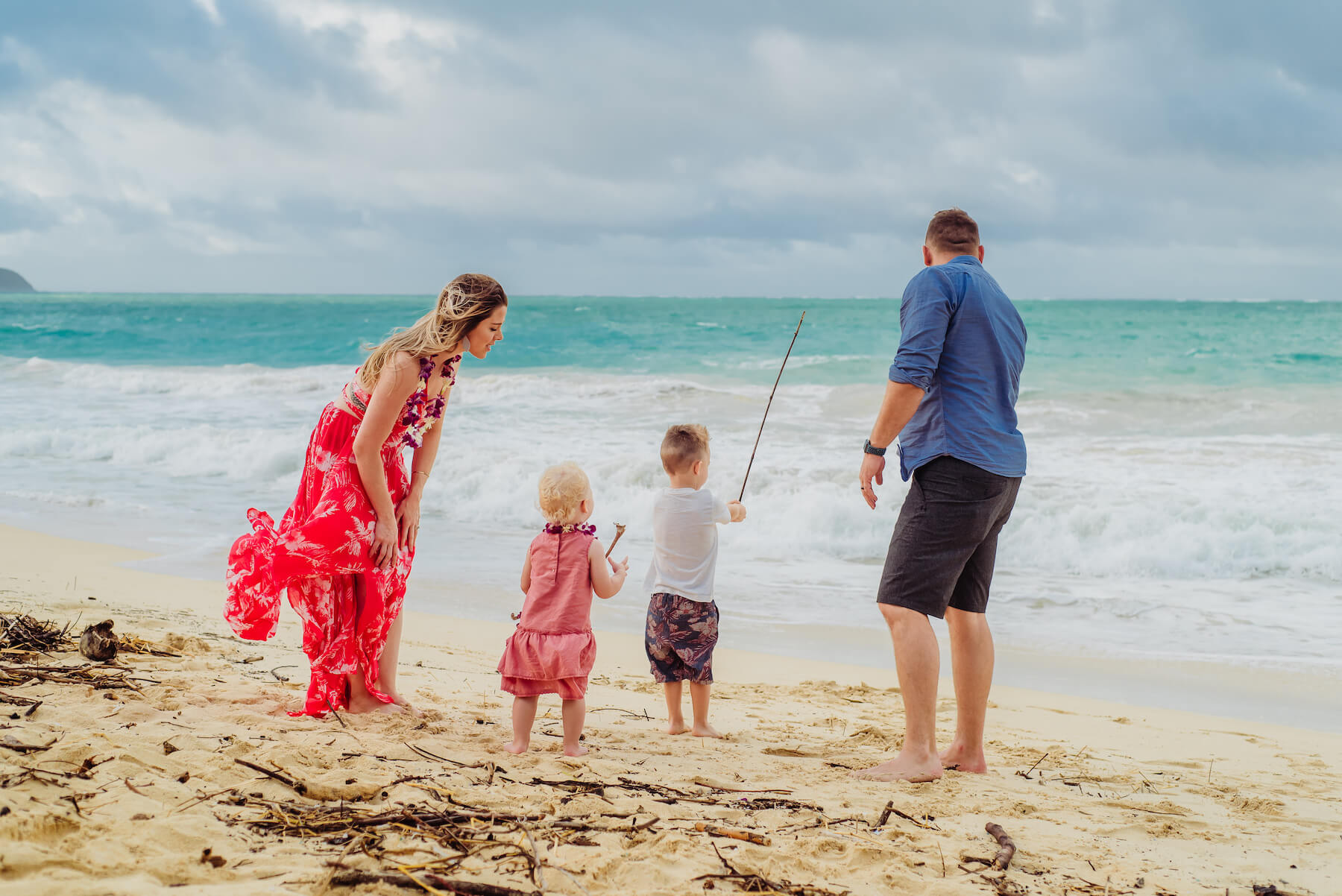 A family fishing in the water and playing on the beach in Honolulu, Hawaii
