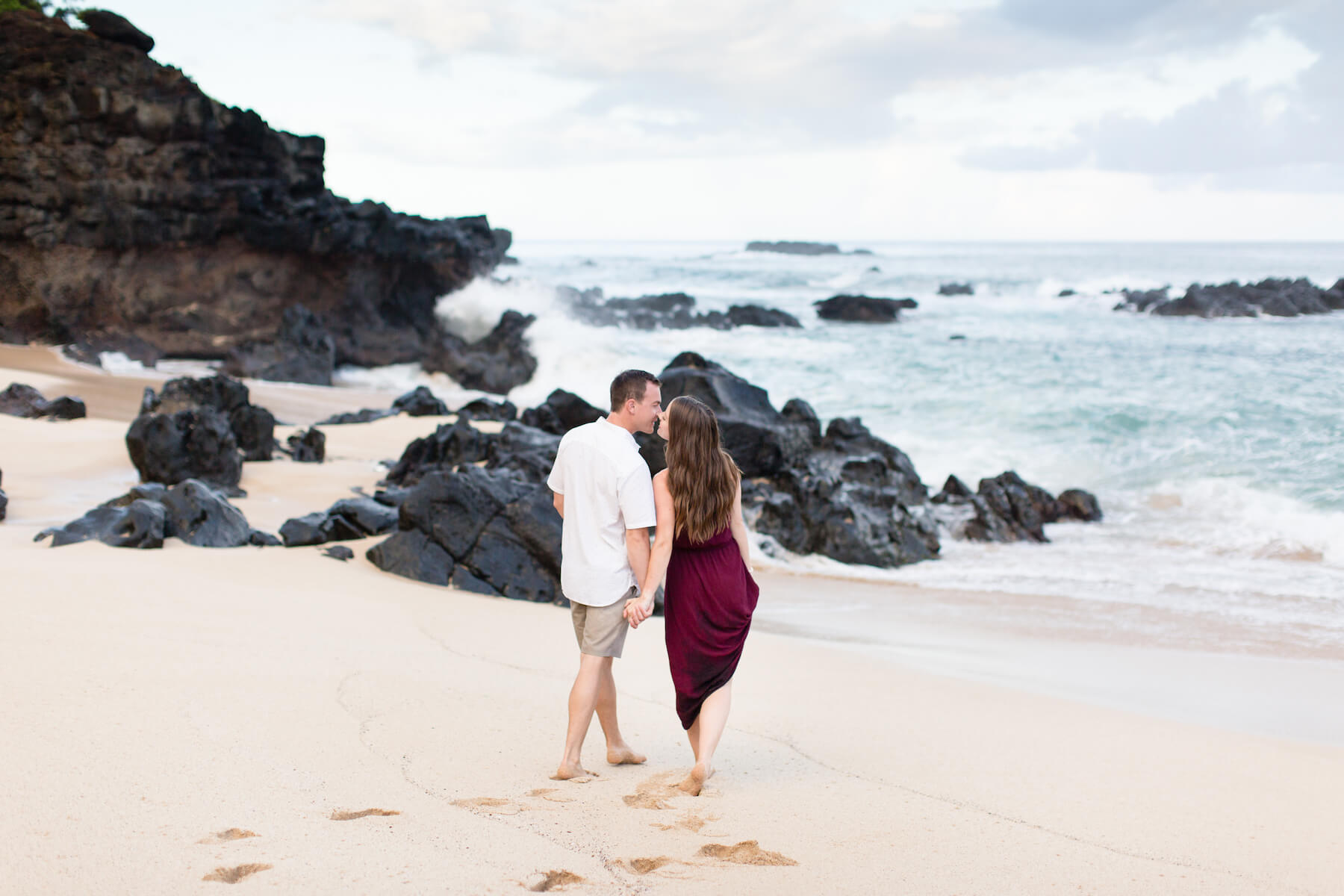 A couple holding hands and looking away from the camera, walking towards the ocean in Honolulu, Hawaii