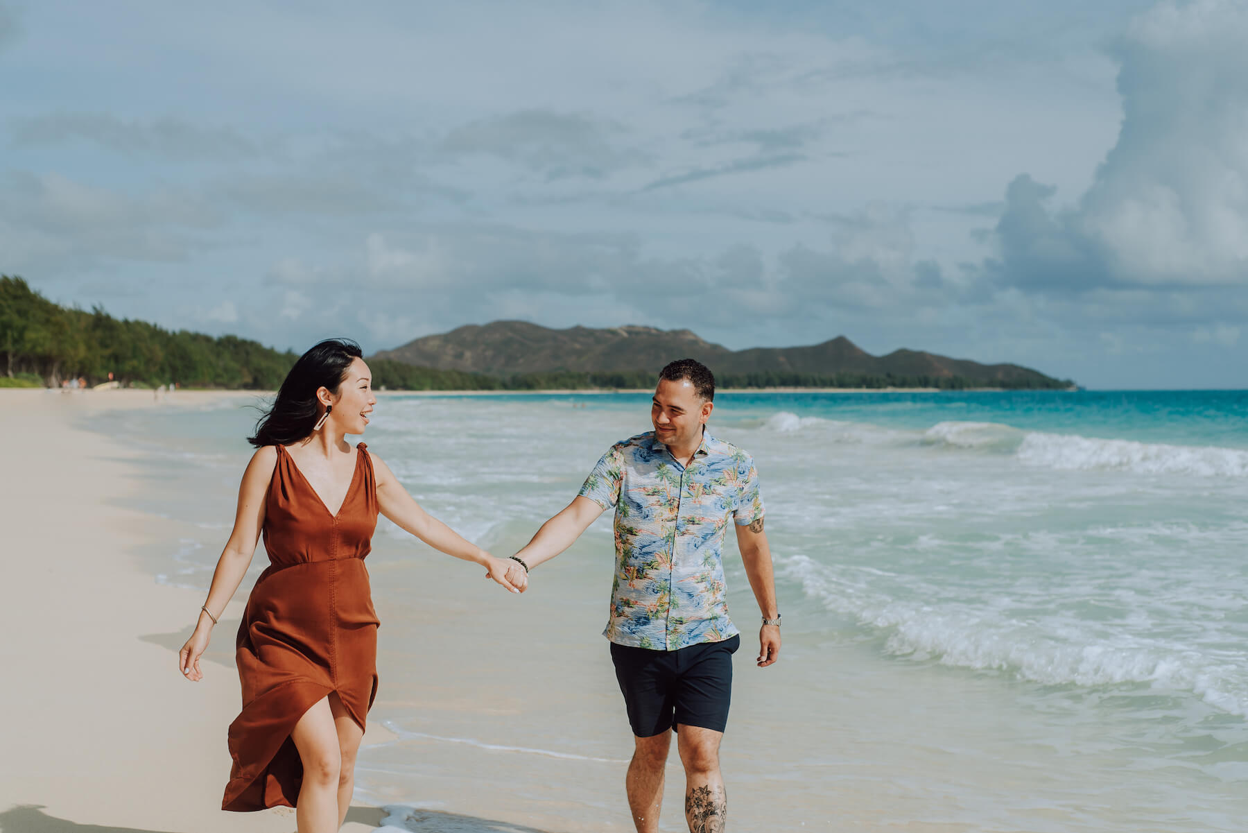 A couple holding hands and walking on the beach in Honolulu, Hawaii