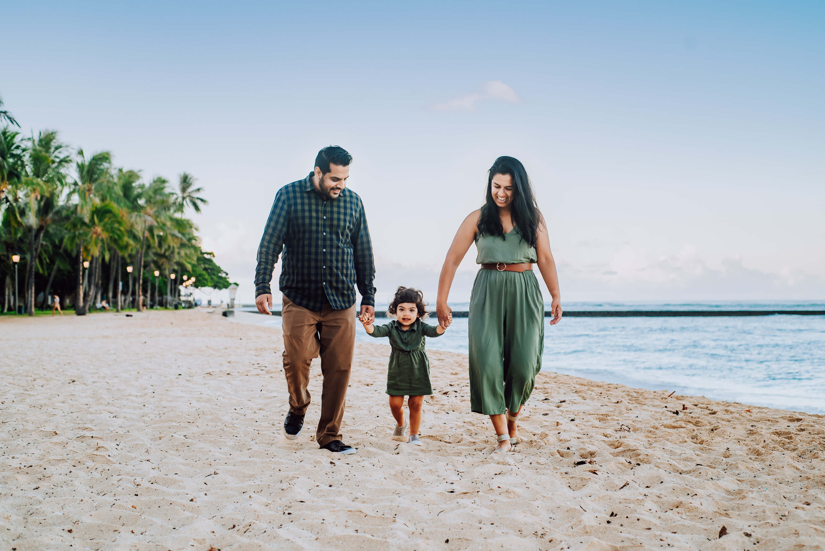 A family holding hands, laughing and walking on the beach in Honolulu, Hawaii