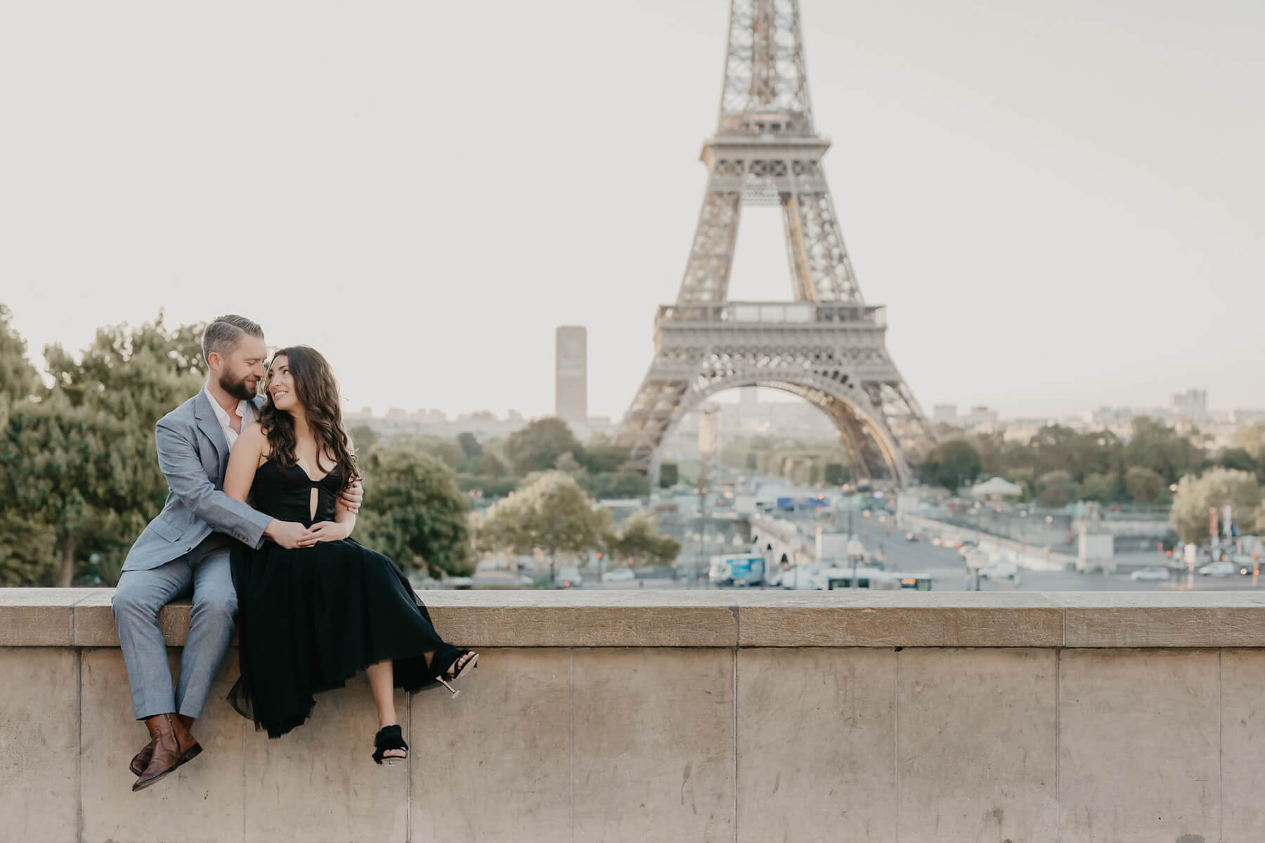 couple sitting in front of the Eiffel Tower in Paris, France