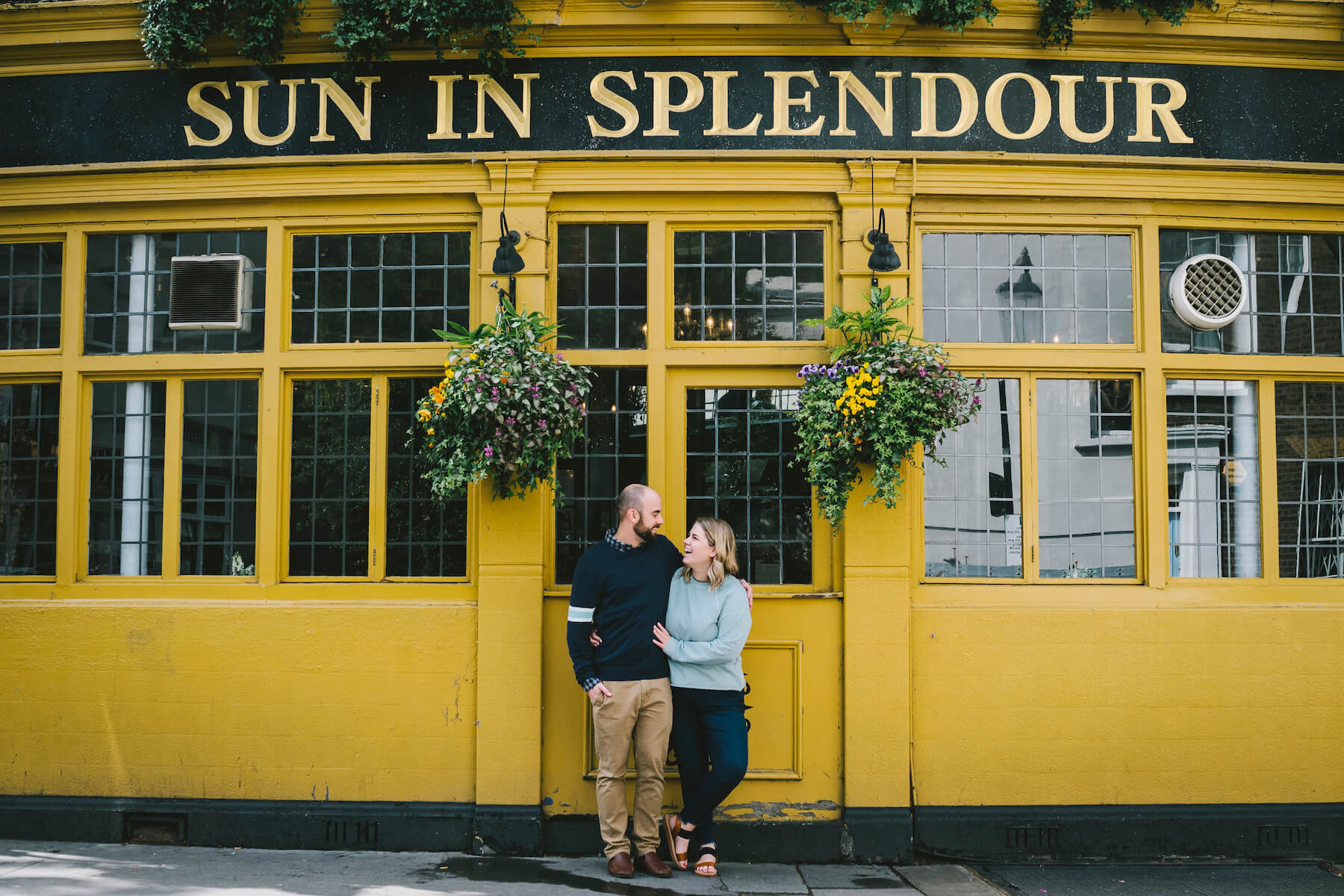 Couple standing in front of Sun in Splendour pub in London, England