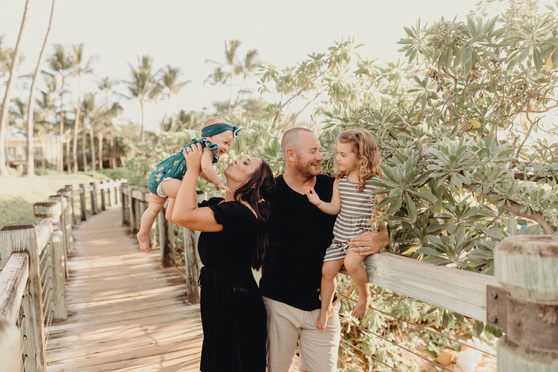 family of four, mom is holding the baby and having fun in Maui, Hawaii
