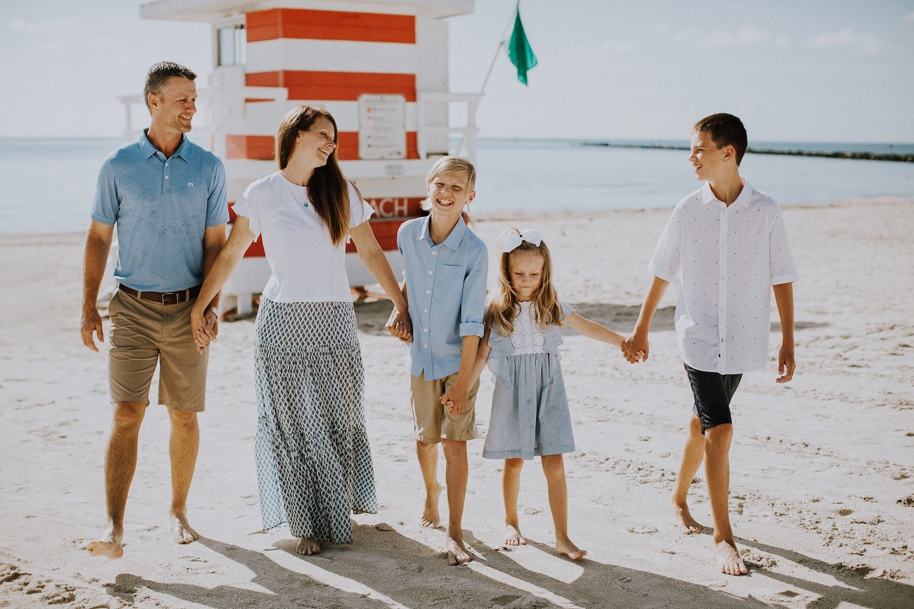family in front of a colourful lifeguard station in Miami, Florida