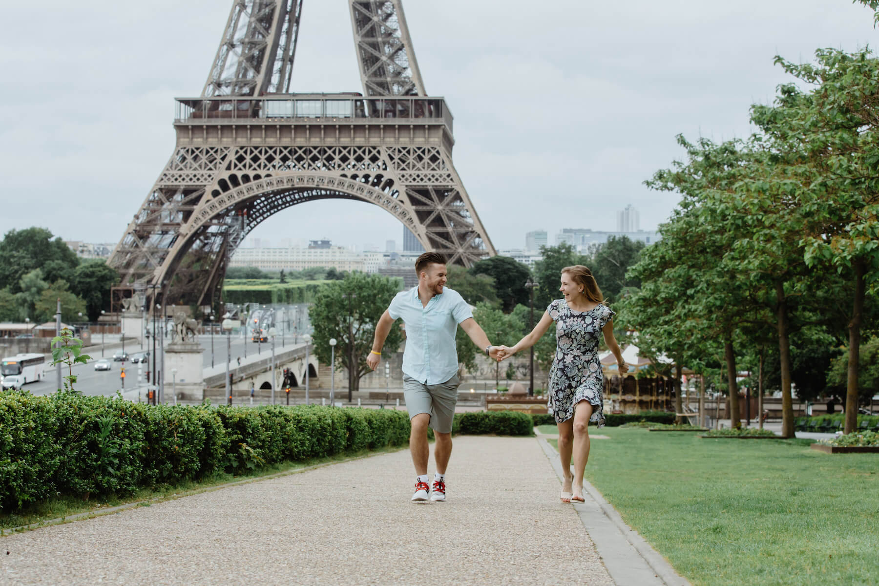 couple holding hands skipping and laughing in front of the Eiffel Tower, Paris, France