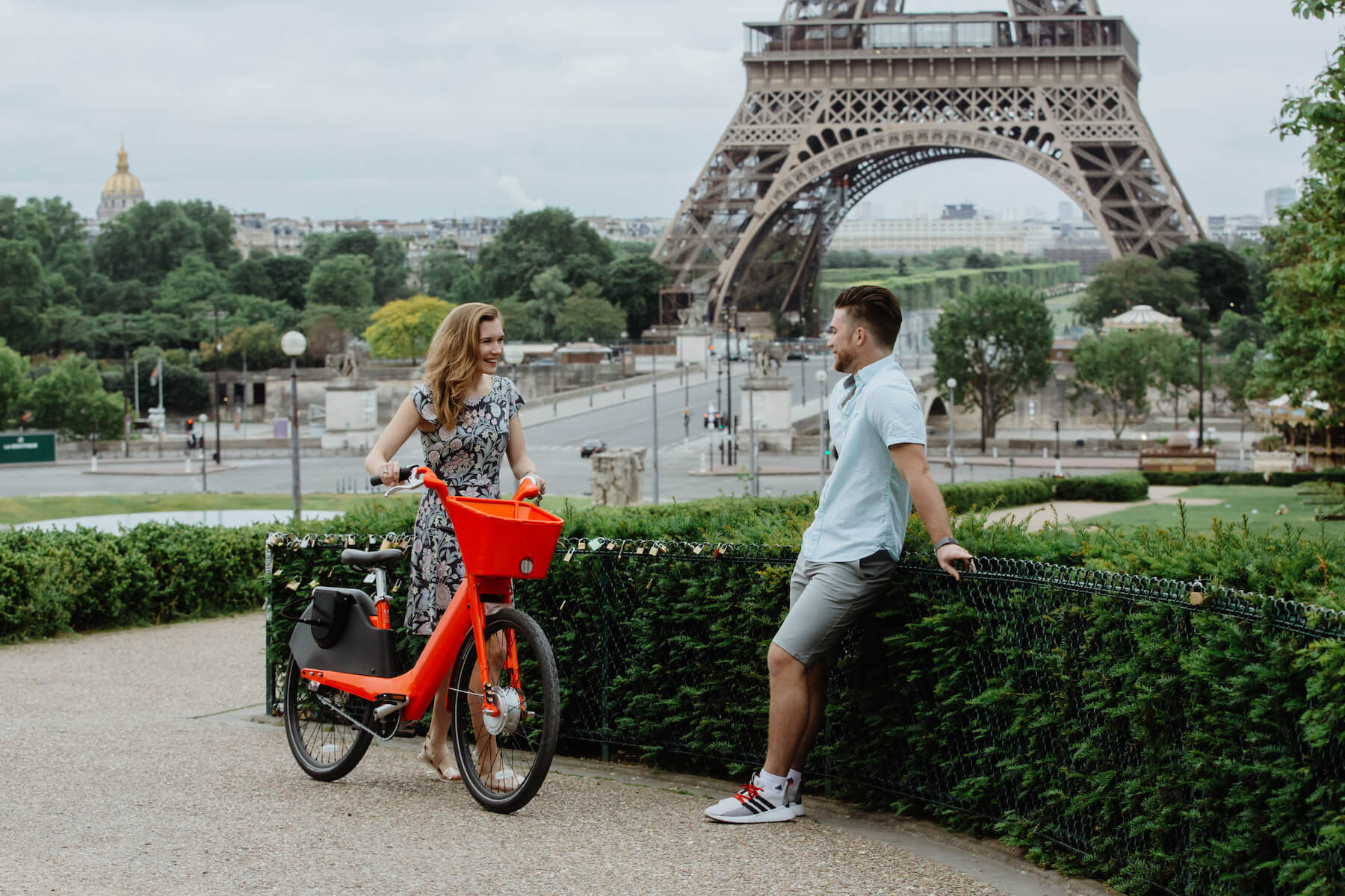 woman with a red bike talking to her finance before the big proposal, in front of the Eiffel Tower, Paris, France